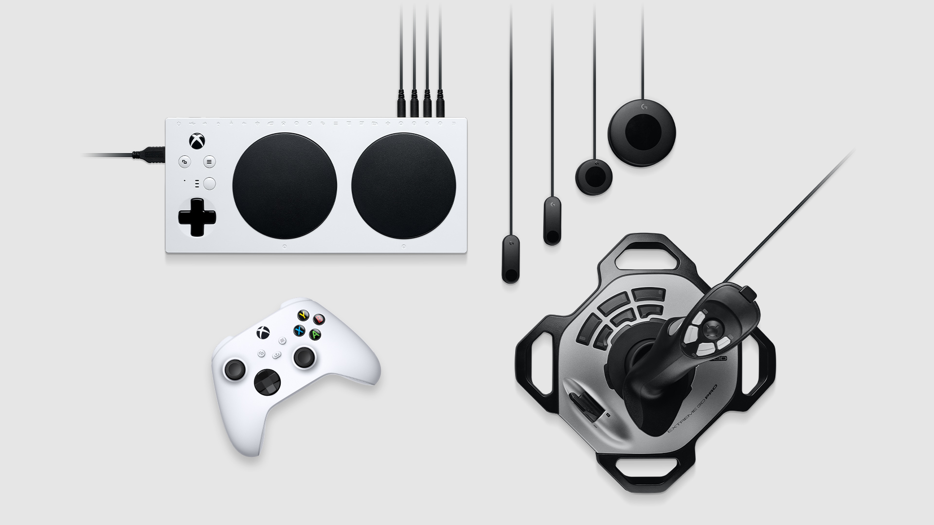Collection of assistive accessories including Xbox adaptive controller, Logitech Adaptive Gaming Kit for Xbox adaptive controller, Xbox wireless controller, and Logitech Extreme 3D Pro Joystick.