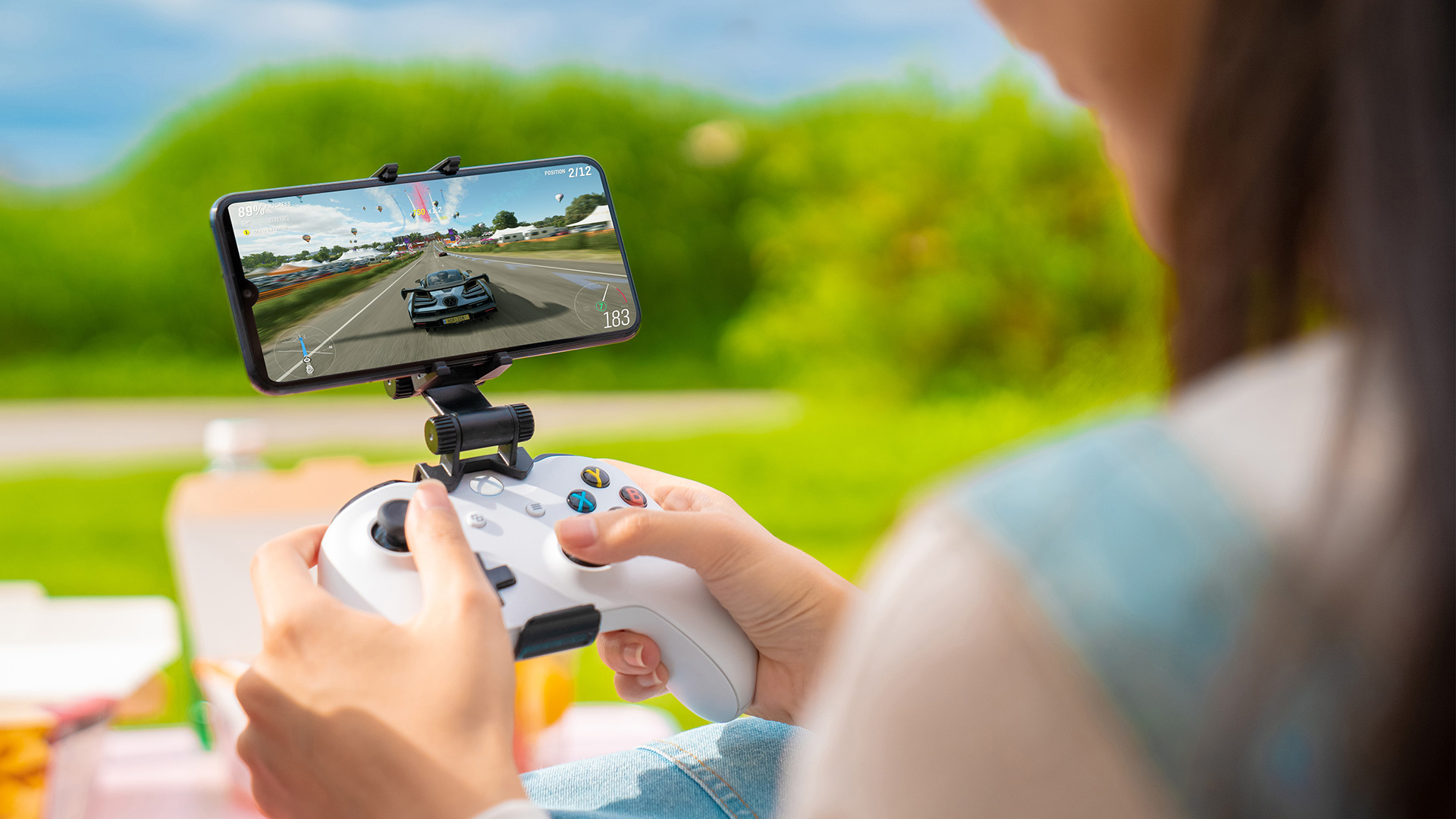 Eine Person hält einen Xbox Wireless Controller, der mit einem mobilen Gerät verbunden ist.