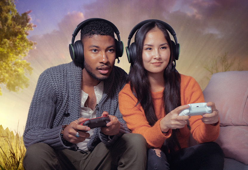 Two people wearing headsets playing Xbox games on a sofa together