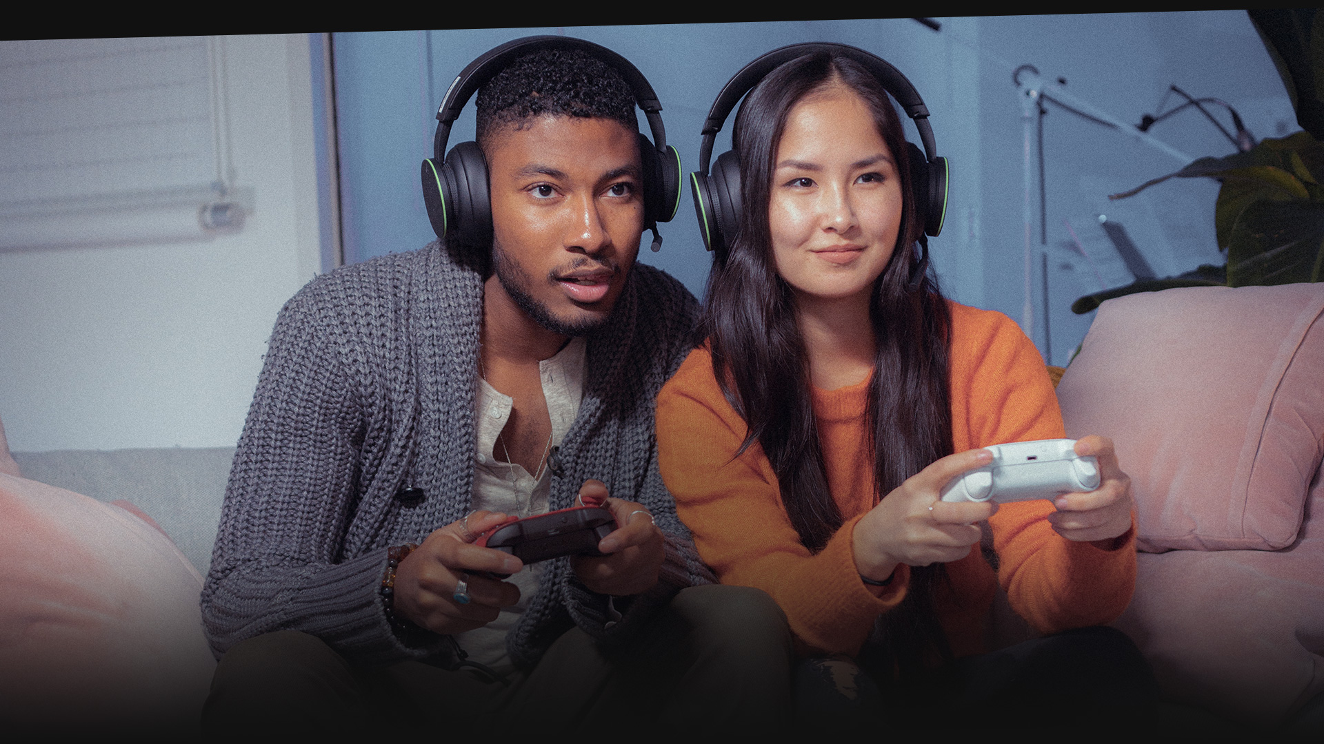 Two people wearing headsets playing Xbox one on a couch